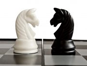 Confrontation of black and white knights on the chessboard.